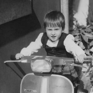 CLAUDIA DAMIANI -  A dispetto della fotografia, in cui la bambina mostra una certa passione per i motori, l'aria aperta ed i viaggi on the road del tipo «Baby, salta su, ti basta uno spazzolino: il resto lo troveremo lungo la strada», leggende familiari narrano che all'età di tre anni la piccola già trascorresse interi pomeriggi sfogliando quotidiani. Si racconta anche che due anni dopo sia stata sorpresa a leggere il vocabolario della lingua italiana, dimostrando molto precocemente un profondo interesse per la tipografia, la stampa e la buona scrittura. Oggi ha scelto i mezzi pubblici per esplorare la giungla cittadina - oltre alle suole delle sue scarpe ungheresi – e continua le sue belle letture in metrò (anche perché in moto sarebbe rischioso).