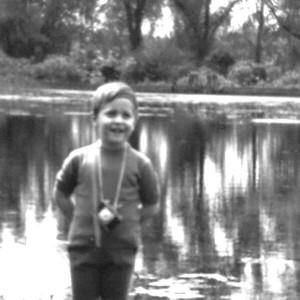 MARCO GIOVENALE -  La macchina fotografica è macchina giocattolo, …anche un po' storta. (Ma pure il fotografato è storto, e forse perfino il lago). C'è comunque più di un sorriso rassicurante, tentativamente ottimista. Altrimenti uno neanche per gioco si dedicherebbe alla fotografia, per quanto in modo ondivago; e non si metterebbe a fare il cercatore (di pagine, di parole). Ma con un lago, un'idea di gioco appunto, e genitori fiduciosi a dar manforte, si può tentare l'avventura, l'inclinazione verbovisiva, in qualche modo.