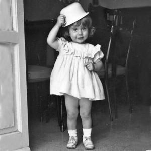 SANDRA ANTONELLI - Sin da piccola ha mostrato subito una certa inclinazione alla stravaganza, tant'è vero che trascorreva interi pomeriggi seduta su una seggiolina – uno sgabello per tavolino – a disegnare e colorare, quando non c'era la mamma a raccontarle fiabe. Invece di pettinare le bambole… Crescendo non è certo migliorata, tanto è vero che dopo la maturità scientifica ha concluso gli studi con un titolo accademico di belle arti, per dedicarsi poi alla progettazione grafica, e perfino all'illustrazione. Si ostina a farlo tuttora, tanto è vero che l'inossidabile amicizia con Fabrizio si perpetua tra le pagine di alcuni preziosi IkonaLiber attraverso cartigli di varia foggia e misura, agghindati per l'occasione d'inchiostro e acquerelli. Qualcosa di buono l'età e gli eventi le hanno portato, però: una sana, invidiabile strafottenza nei riguardi della buona creanza e delle convenzioni; cosa che era già in nuce nella foto, vista l'originalità del cappello, che … neanche Coco Chanel.